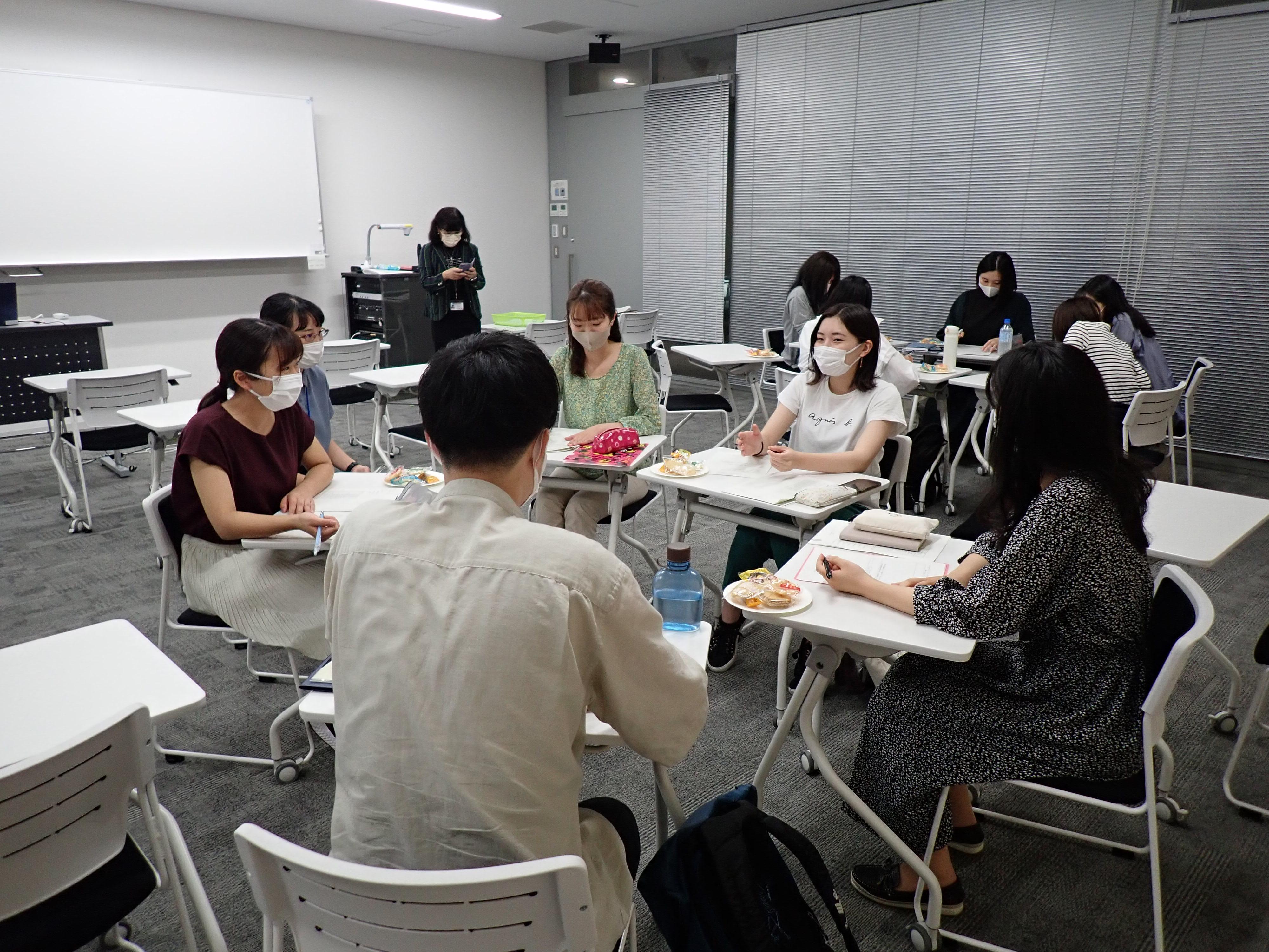 グループごとに机を寄せて話し合っている学生たちの写真