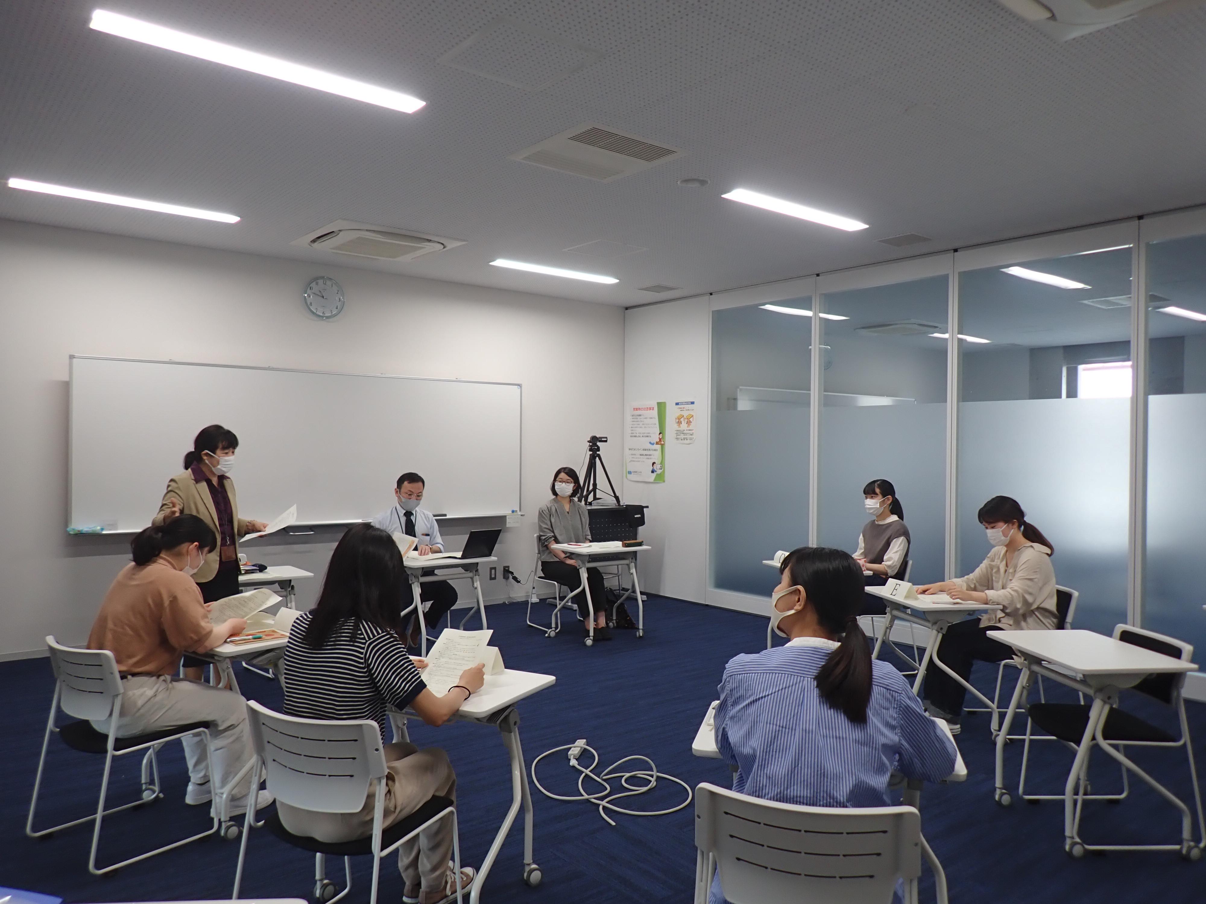 学生がメモをとりながら話を聞いている写真
